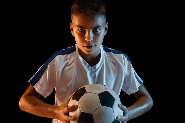 Young boy as a soccer or football player in sportwear on dark wall.