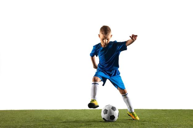 Giovane ragazzo come un giocatore di calcio o di calcio in abbigliamento sportivo che fa una finta o un calcio con la palla per un gol sul muro bianco.