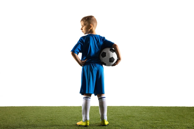 Young boy as a soccer or football player in sportwear standing with the ball like a winner, the best forward or goalkeeper on white wall. fit playing boy in action, movement, motion at game.