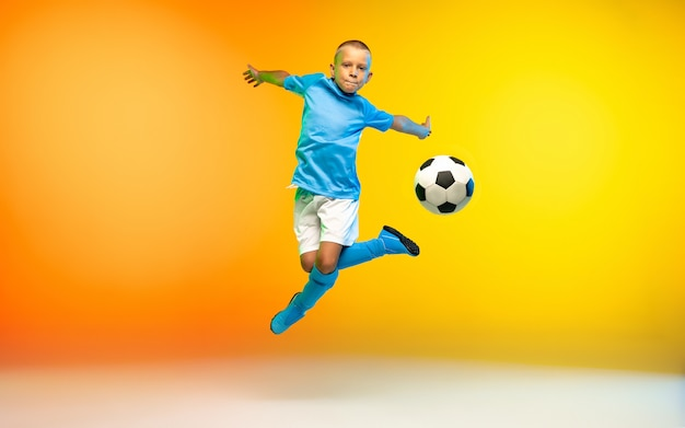 Young boy as a soccer player in sportwear practicing on gradient yellow in neon