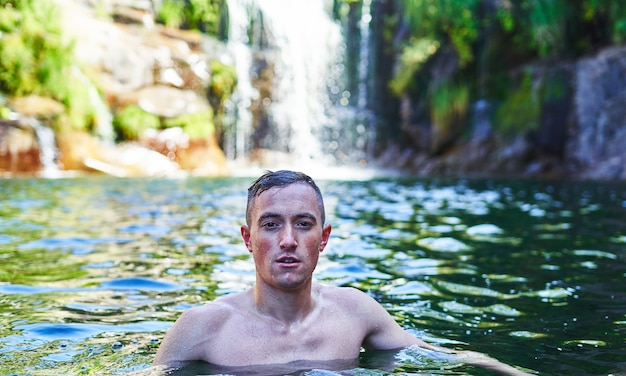 Young boy bathes in natural pool with waterfall.