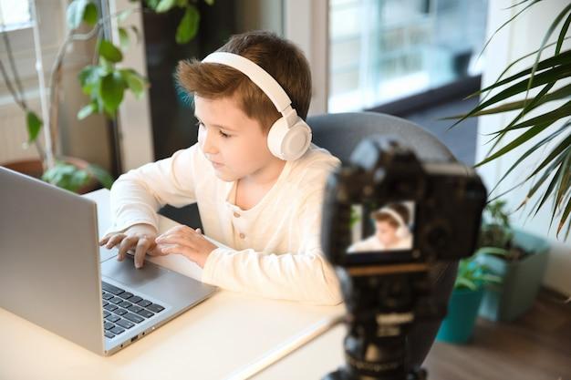 어린 소년 블로거는 팔로워들과 의사 소통을하여 비디오 나 스트림을 만듭니다. 새로운 직업으로서의 블로깅. 아이 엄지를 웃고 비디오 카메라를 찾고 있습니다.