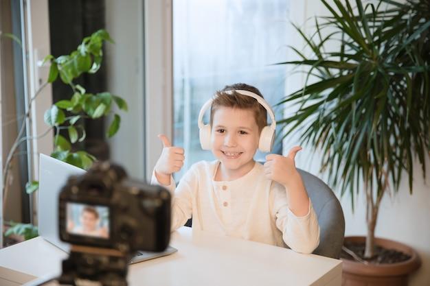 어린 소년 블로거는 팔로워들과 의사 소통을하여 비디오 나 스트림을 만듭니다. 새로운 직업으로 블로깅. 아이 엄지를 웃고 비디오 카메라를 찾고 있습니다.