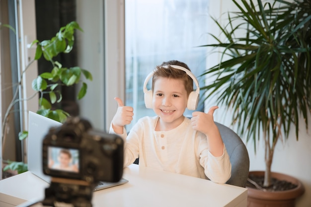 Young boy blogger communicates with his followers, making video or stream. blogging as a new proffesion. smiling kid thumb up and looking to video camera.