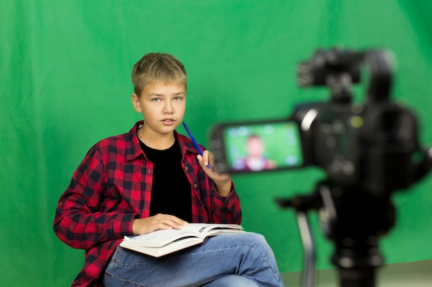 Young boy blogger records video on a green