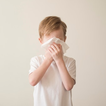 Young boy blowing nose