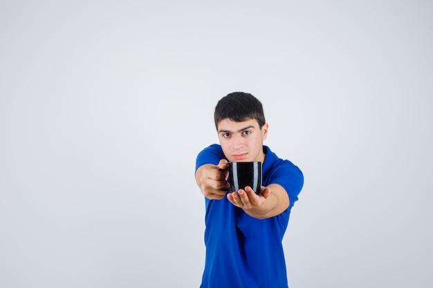 Giovane ragazzo in t-shirt blu che tiene tazza, dandolo a qualcuno e guardando fiducioso, vista frontale.