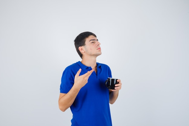 Giovane ragazzo in maglietta blu che tiene tazza, allungando la mano in modo interrogativo e guardando pensieroso, vista frontale.