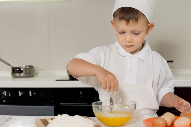 Young boy breaking eggs into a mixing bowl as he stands in his chefs hat and apron baking a cake