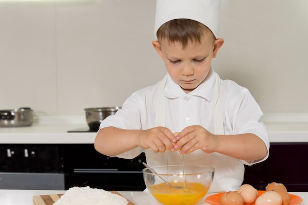 Young boy breaking fresh eggs into a bowl