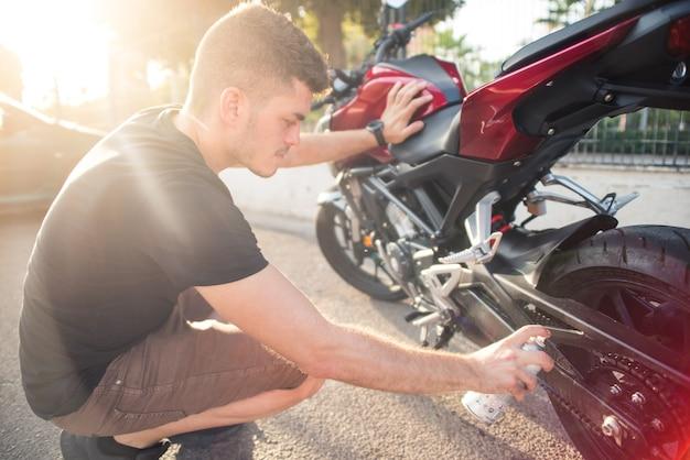 오토바이의 체인을 야외에서 청소하는 어린 소년. 오토바이 청소 및 유지 관리 개념입니다. 진짜 사진.