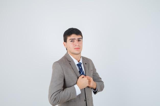어린 소년 공식적인 양복에 가슴 위에 주먹을 떨림과 자신감을 찾고 있습니다. 전면보기.
