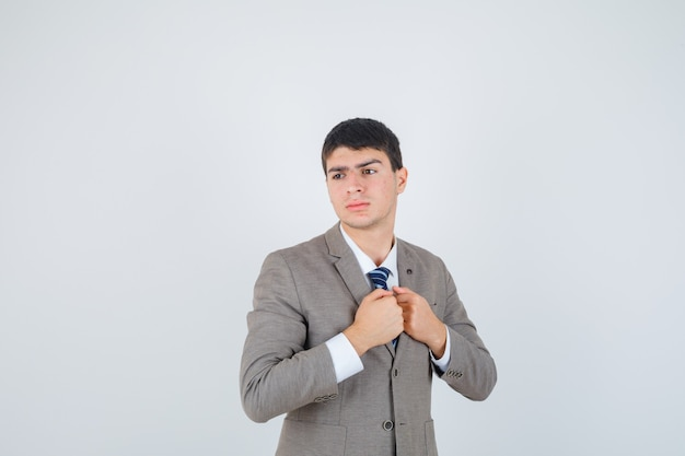 胸に拳を握りしめ、フォーマルなスーツを着て目をそらし、物思いにふける少年。正面図。