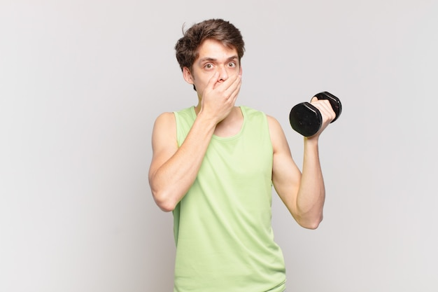 Young boy covering mouth with hands with a shocked, surprised expression, keeping a secret or saying oops. dumbbell concept