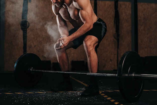 Young boy dead lifting a barbell in a crossfit gymnasium.