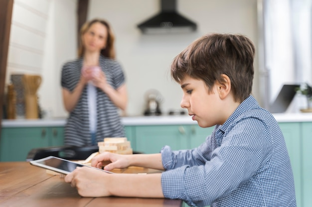 Молодой мальчик делает свою домашнюю работу на планшете