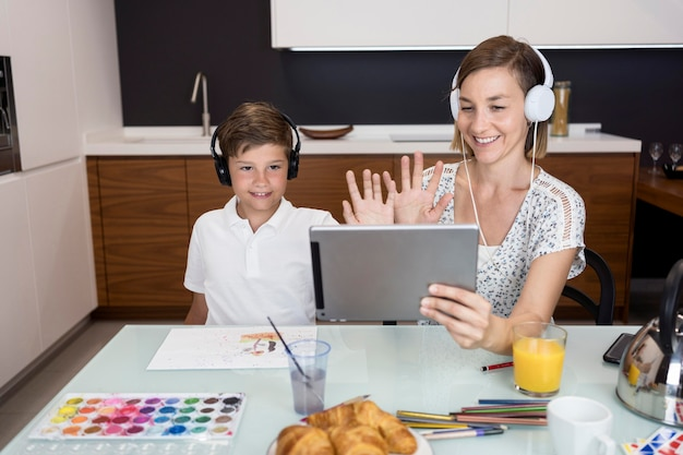 Young boy doing video conference together with mother