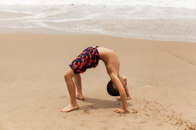 Young boy doing wheel pose on sandy beach, yoga practice in the morning