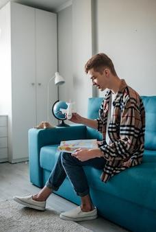 Мальчик мечтает о путешествии, сидя на синем диване с картой и игрушечным самолетом.