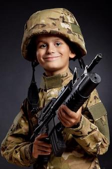 Молодой мальчик одет как солдат с винтовкой
