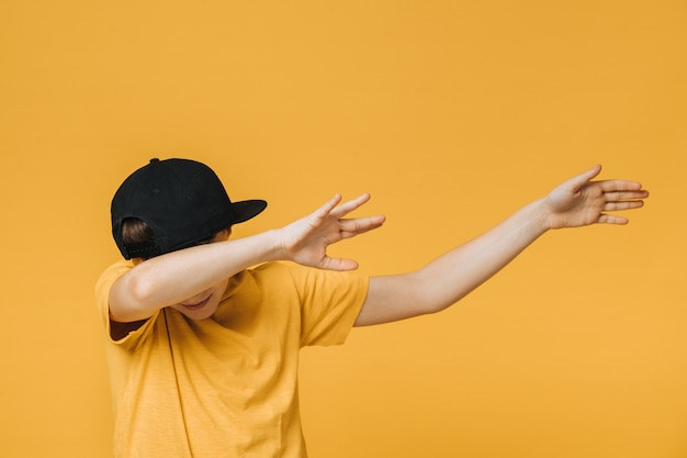 Young boy dressed in yellow t-shirt and black baseball cap over yellow background makes teenagers dab gesture, moves his hands aside, covering his face, that means i did it. youth culture concept.