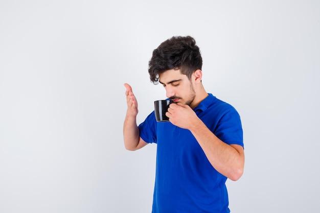 お茶を飲み、青いtシャツを着て手を伸ばして、真剣に見える少年、正面図。