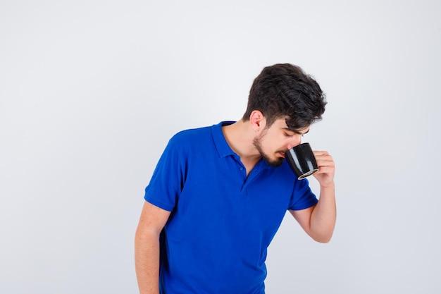 青いtシャツでお茶を飲み、真剣に見える少年。正面図。
