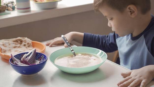 若い男の子はダイニングルームのテーブルに座っているスープを食べる