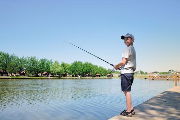 어린 소년은 여름 화창한 날 호수나 연못에서 낚시를 즐깁니다.