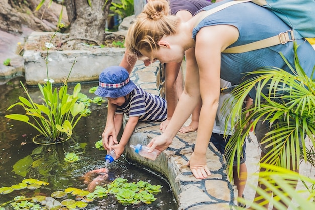 우유 병으로 잉어 물고기를 먹이 어린 소년.