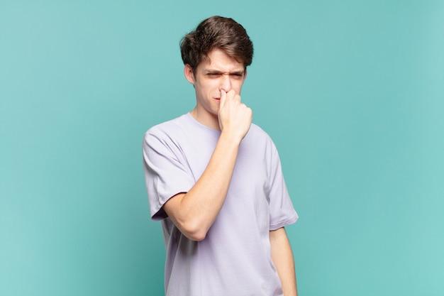 嫌悪感を感じ、悪臭や不快な悪臭を避けるために鼻をかむ少年