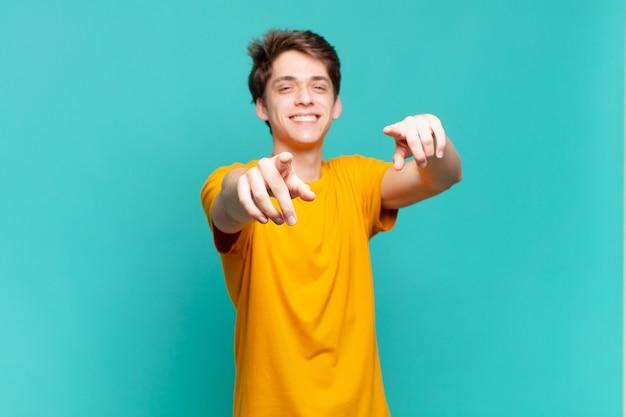 행복하고 자신감을 느끼는 어린 소년은 두 손으로 카메라를 가리키고 웃고, 당신을 선택합니다