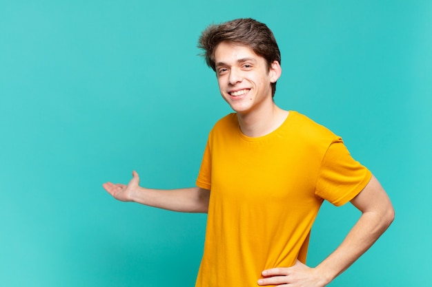 Young boy feeling happy and cheerful, smiling and welcoming you, inviting you in with a friendly gesture