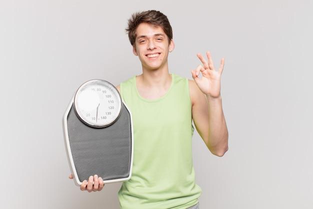 어린 소년은 행복하고 편안하며 만족하며 괜찮은 제스처, 웃는 규모 개념으로 승인을 보여줍니다.