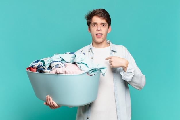 행복하고, 놀라고, 자랑스러워하는 어린 소년, 흥분하고 놀란 표정으로 자신을 가리키며 옷을 세탁하는 개념