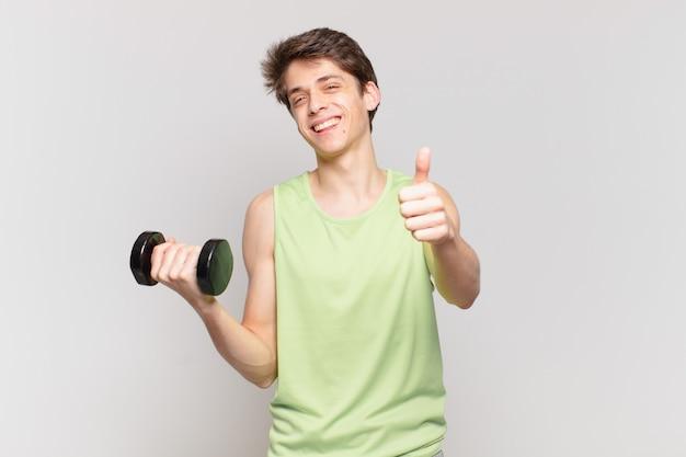 誇り高く、のんきで、自信を持って幸せに感じ、親指を立てて前向きに笑っている少年。ダンベルのコンセプト