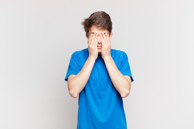 悲しみ、欲求不満、神経質、落ち込んでいる少年、両手で顔を覆い、泣いている