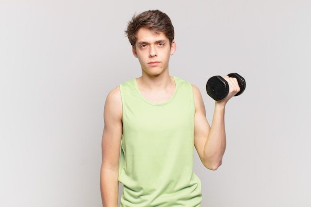 Young boy feeling sad, upset or angry and looking to the side with a negative attitude, frowning in disagreement. dumbbell concept