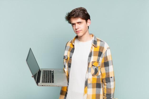 悲しみ、動揺、怒りを感じ、否定的な態度で横を向いて、意見の相違に眉をひそめている少年。ノートパソコンのコンセプト