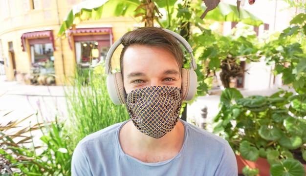 Молодой мальчик фокусируется в камере с наушниками и маской для лица - новая концепция образа жизни