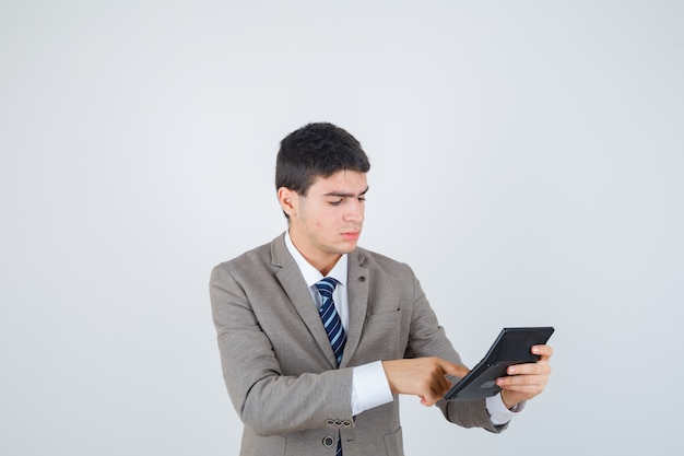 Giovane ragazzo in abito formale che tiene calcolatrice, facendo alcune operazioni su di esso e guardando concentrato, vista frontale.