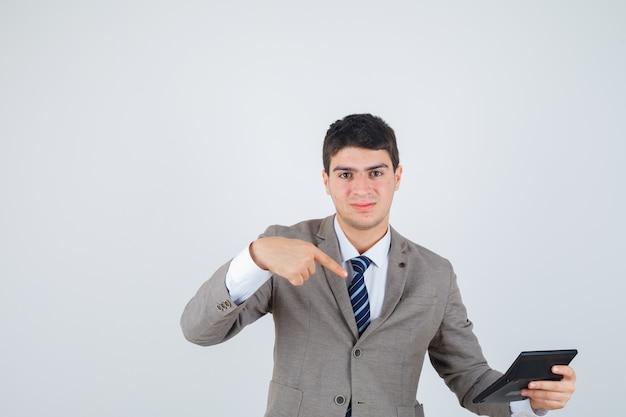 Giovane ragazzo in abito formale tenendo la calcolatrice, indicandola e guardando allegro, vista frontale.