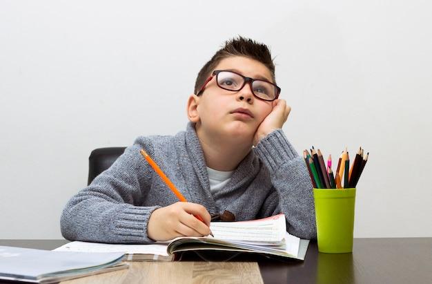 어린 소년 숙제 집에서 쓰는 좌절 된. 테이블에서 공부하는 소년. 연필로 그리는 아이.