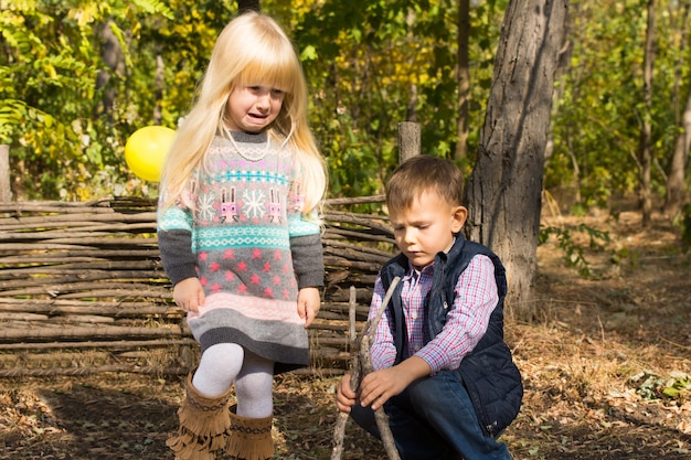 Young boy and girl playing together outdoors in woodland building a small wooden wigwam from twigs and branches as they enjoy a carefree day in nature