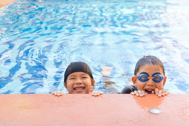 Young boy and girl swimming in pool.