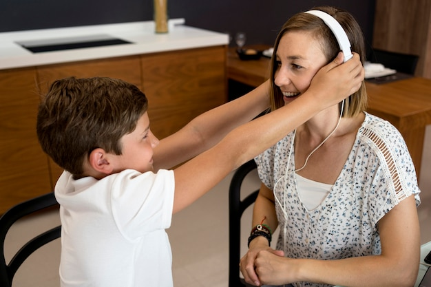 Молодой мальчик дает наушники своей матери