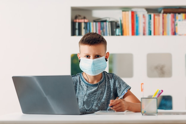Young boy in headset sitting at table with laptop and medical face mask and preparing to school