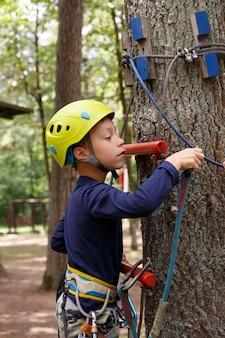 Young boy in helmet spend his leisure time in adventure playground.