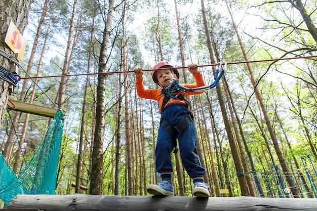 Young boy in helmet walks by pendant tree log