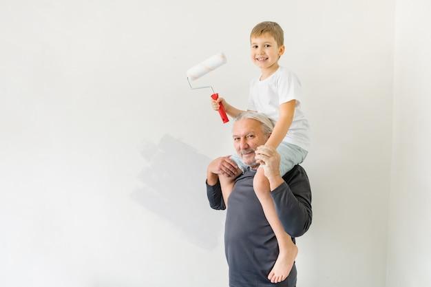 새 집으로 이사 한 후 할아버지가 벽을 칠하는 것을 돕는 어린 소년. 아파트 수리.